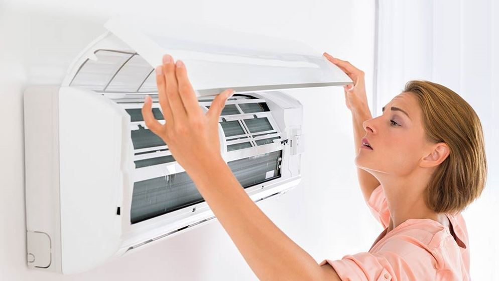 woman checking filters on air conditioner